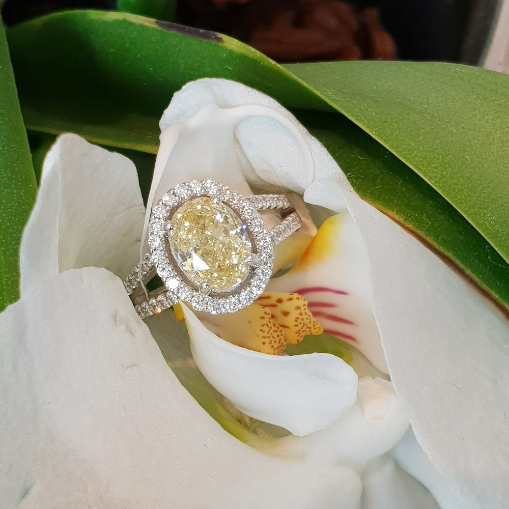 18kt white gold ring with fancy yellow oval cut diamond